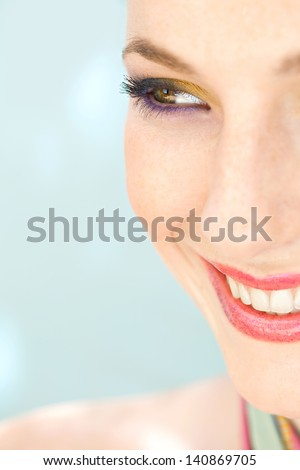 Close up beauty portrait of an attractive young woman half face wearing colorful summery make up, smiling happy against a blue background, looking away. - stock photo