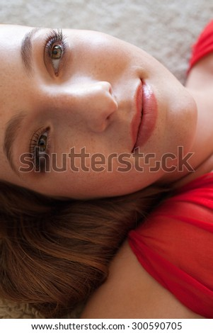 Close up beauty portrait of an attractive young woman laying down on a bed, in a bright red dress, looking happy, thoughtful and serene, home interior. Beautiful woman lifestyle, relaxing indoors. - stock photo
