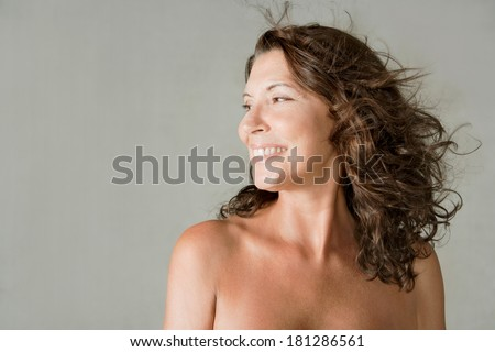 Close up beauty portrait of an elegant mature woman with bare shoulders, smiling against a plain gray wall background while her hair is flying and floating in the breeze. Beauty lifestyle. - stock photo