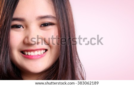 Close-up beauty portrait of Asian female model smiling, over soft pink background for copy space - stock photo
