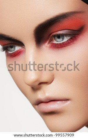 Close-up beauty portrait of attractive model face with bright fashion make-up. Devil style visage for Halloween - stock photo