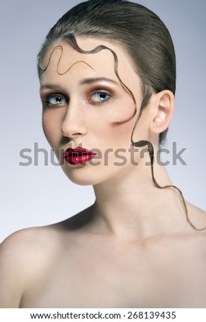 close-up beauty portrait of sensual woman with cute make-up, red lipstick and creative decorative hairdo with some lock on her face  - stock photo