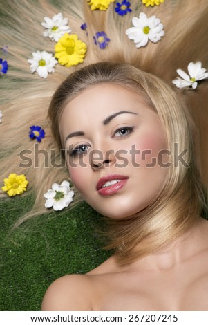 close-up beauty portrait of stunning female  with perfect skin and natural make-up lying on green grass with some colorful flowers in smooth and long hair  - stock photo