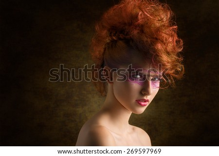 close-up beauty portrait of very pretty woman with punk hair-style and make-up and aggressive expression. Looking in camera. Perfect skin, creative rock style  - stock photo