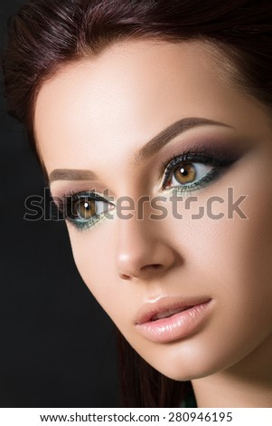 Close-up beauty portrait of young pretty brunette model with fashion smokey eyes make-up. - stock photo