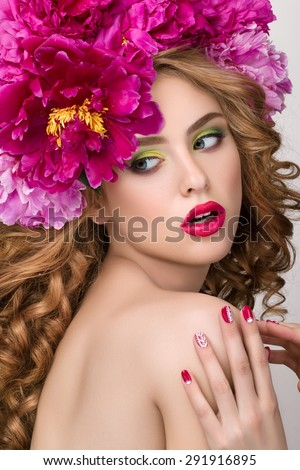 Close-up beauty portrait of young pretty surprised girl with flower wreath wearing bright pink lipstick, touching her lips. Bright modern summer makeup. Beauty, spa, manicure and skincare concept - stock photo