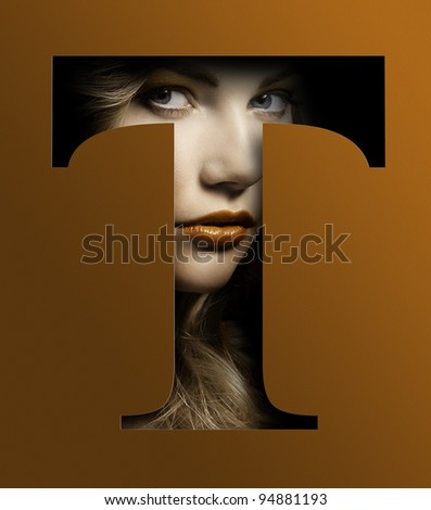 close up beauty portrait of young pretty woman behind a color orange letter T - stock photo