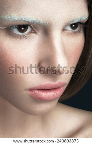 Close up beauty portrait of young women/girl with brown eyes, pink lipstick, white eyeliner on dark background. - stock photo