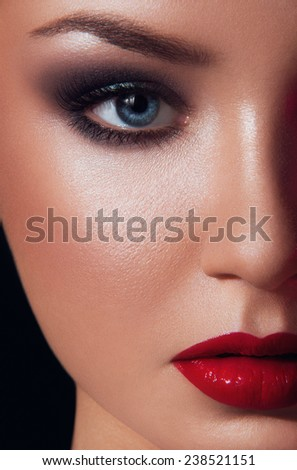 Close up beauty portrait of young women with blue eyes, red make up looking at you on black background - stock photo