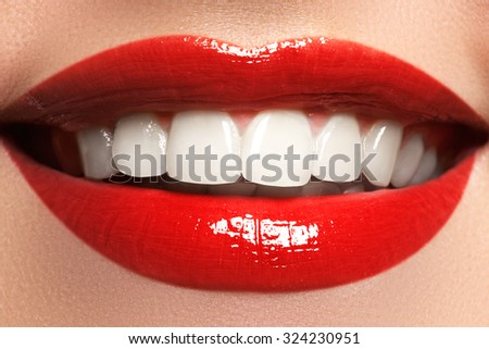Close up  beauty portrait view of a young woman natural smile with red lips. Classic beauty detail. Red lipstick and white teeth. Closeup of woman smiling with prefect white teeth. - stock photo
