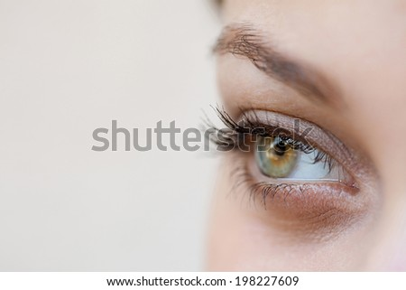 Close up beauty portrait view of an attractive young woman eye and pupil looking up to the side, being thoughtful and calm, wearing cosmetics. Healthy skin, sight and beauty care, wellness. - stock photo
