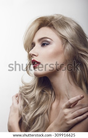 Close-up beauty shot of a beautiful young blonde women with the wind in her hair and sensuality in the eyes. Gently touching her face.  - stock photo