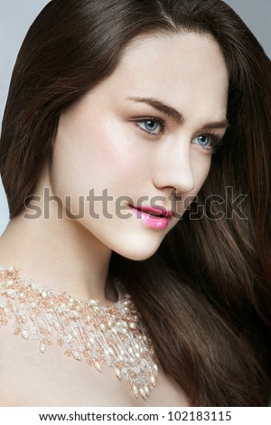 Close-up beauty shot of professional caucasian model with brown hair and jewelery necklace