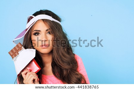 Close-up Beauty teen model girl eating milk chocolate plate.Beautiful Surprised young woman takes chocolate sweets,smiling and having fun. Funny girl, professional make up and bow hairstyle.studio  - stock photo