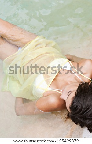 Close up beauty view of an attractive young woman laying on the shore of a spa natural swimming pool submerged in clear waters and relaxing while on a summer holiday. Beauty and healthy lifestyle. - stock photo