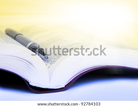 Close-up Bible with pen with yellow rays - stock photo