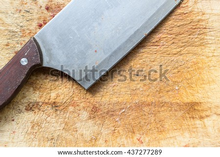 Close up big knife on rough wooden chopping block with bits of chicken - stock photo
