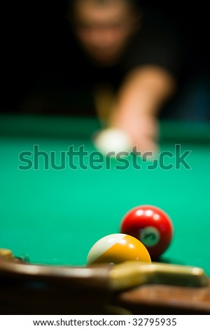 Close up billiard ball on the billiard table and unfocused player on the background - stock photo