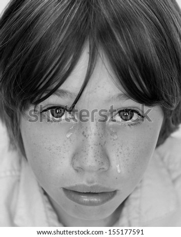 Close up black and white image of young boy looking distressed and sad with tears running down his cheeks.                                - stock photo
