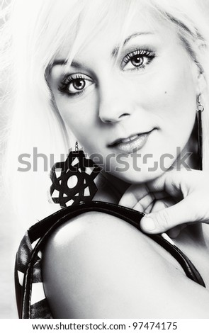 Close-up black and white portrait of a young blond woman with earrings - stock photo