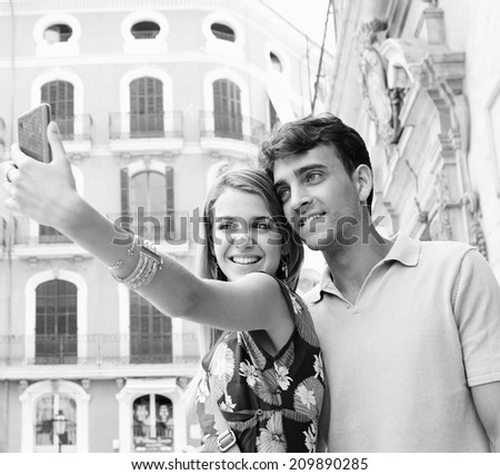 Close up black and white portrait of an attractive young couple relaxing and taking a selfie photo of themselves while visiting a destination city on holiday, together outdoors. Technology lifestyle. - stock photo