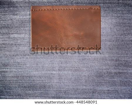 Close up blank brown leather jean label over denim background