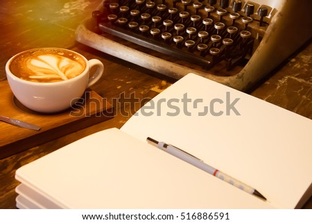 Close up Blank Notebook and vintage typewriter on the wooden table with coffee