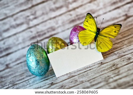 Close up Blank White Greeting Card, Yellow Green Butterfly Insect and Colored Easter Chocolate Eggs on Top of a Wooden Table with Fuzzy Background. - stock photo