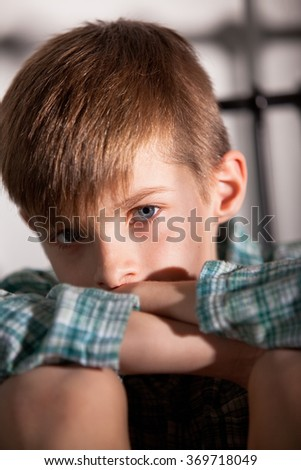 Close up Blond Young Boy with Knees Up and Folded Arms, Looking Straight at the Camera with Sad Facial Expression. - stock photo