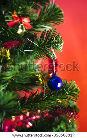 close up blue christmas ball on tree on red background - stock photo