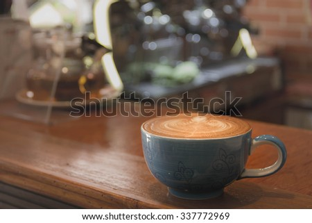 Close up blue cup of Coffee, latte on the wooden table - stock photo