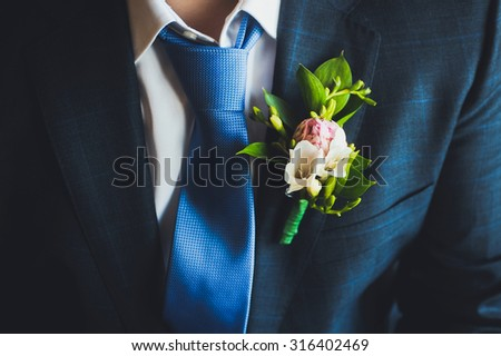 close-up blue jacket groom on their wedding day with a tie and lapel buttonhole - stock photo
