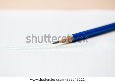 close-up blue pencil on graph paper background - stock photo