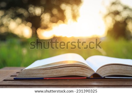 Close up book on table in sunset time - stock photo