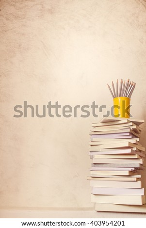 Close up book stacked  with the  concrete wall background , vintage color tone for knowledge concept - stock photo