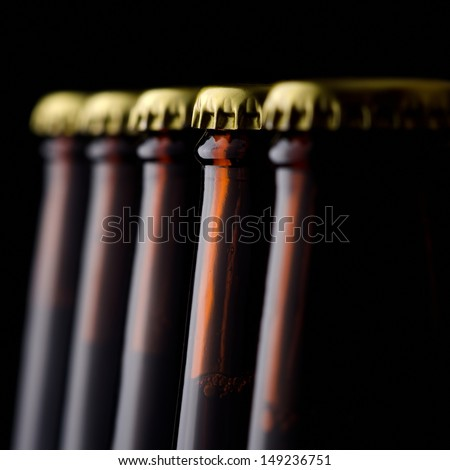 Close up bottles of beer on a black background - stock photo