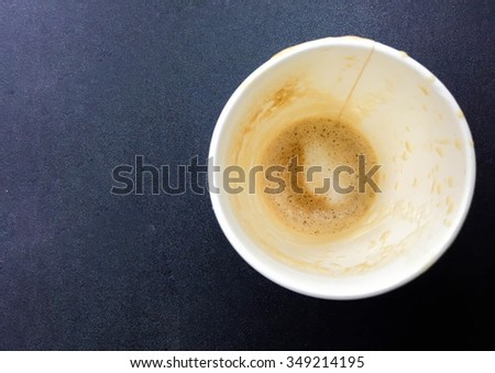close up  bottom of empty paper cup of coffee on black table background