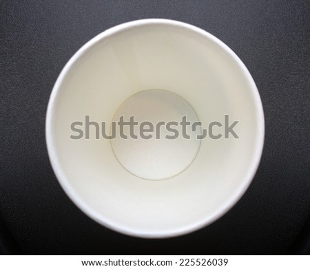 close up bottom of empty recycle paper cup on dark background texture - stock photo