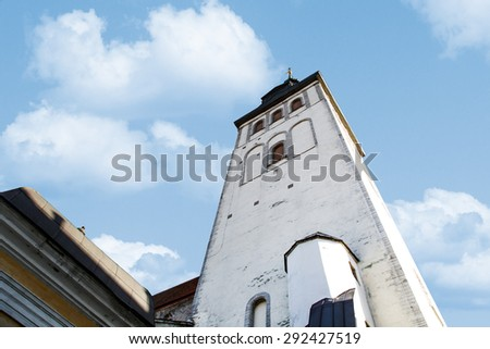 Close up bottom view of the medieval former St Nicholas Church, on blue cloudy sky background. - stock photo