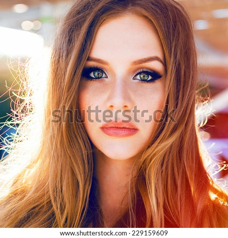 Close up bright fashion portrait of beautiful young woman with big green eyes natural make up and long blonde hairs posing on sunset at the beach. - stock photo