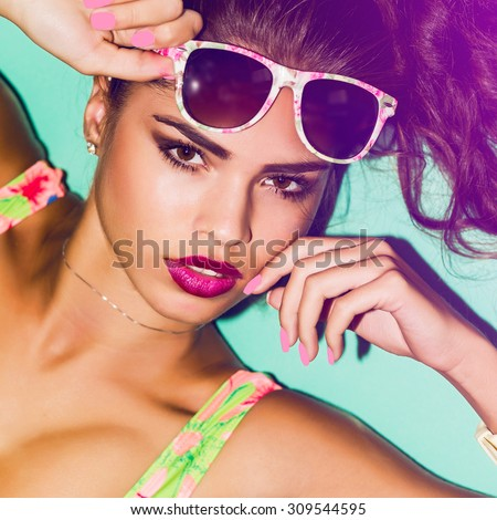 Close up bright summer fashion portrait of stylish beautiful  woman with  amazing make up,  colorful sunglasses  and pink nails. Indoor  beauty image. Model with perfect skin. Blue background,