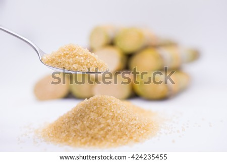 Close up brown Sugar.brown sugar in spoon.brown sugar in wooden spoon.  brown sugar on sugarcane blur background.brown sugar. brown sugar from sugar cane. brown sugar.natural brown sugar.brown sugar. - stock photo