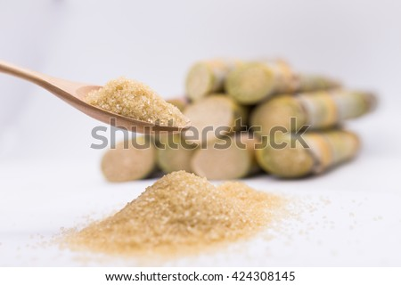 Close up brown Sugar.brown sugar in spoon.brown sugar in wooden spoon.  brown sugar on sugarcane blur background.brown sugar. brown sugar from sugar cane. natural brown sugar.brown sugar. - stock photo