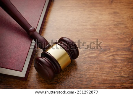 Close up Brown Wooden Gavel and Maroon Book on Top of Wooden Table, Emphasizing Legal or Law Concept - stock photo