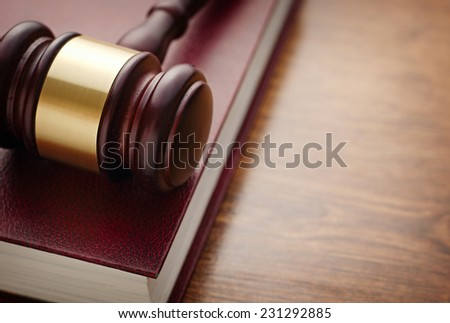 Close up Brown Wooden Gavel and Maroon Book on Top of Wooden Table, Emphasizing Legal or Law Concept