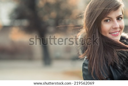 Close up brunette portrait with natural look, head shot of a young sexy woman on blurred background, soft sunny colors. Copyspace - stock photo