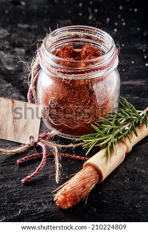 Close Up Brush and Cayenne Marinade Powder Container for Meat on Table - stock photo