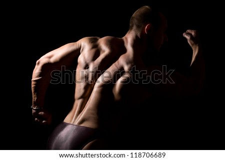 Close-up build muscle bodybuilder on a dark background - stock photo