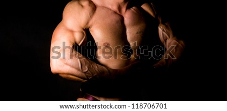 Close-up build muscle bodybuilder on a dark background