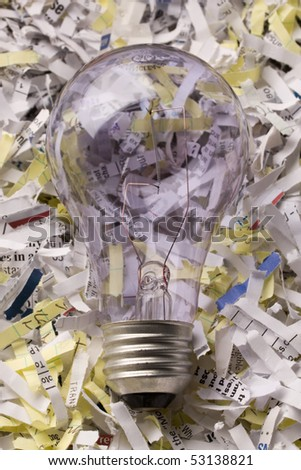 Close up bulb laying on a pile of shredded paper.  Concept of recycle or environmental topic. - stock photo